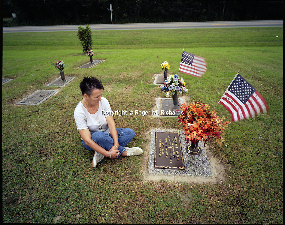 "Rose Merry Tuazon, the mother of 21-year-old U.S. Army soldier Andrew Tuazon, mourns at her son's grave at Greenlawn Cemetery in Chesapeake, VA, on October 20, 2005. Andrew Tuazon was shot in the head by an Iraqi sniper in the city of Mosul in northern Iraq on May 10, 2004. His mother visits his grave every day. She now drives her son's Honda Accord, with the license plate bearing the inscription ""RIP Andy"". (Photograph by Roger M. Richards"