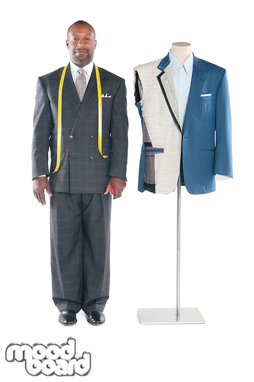 Portrait of tailor in formal wear standing besides a dummy