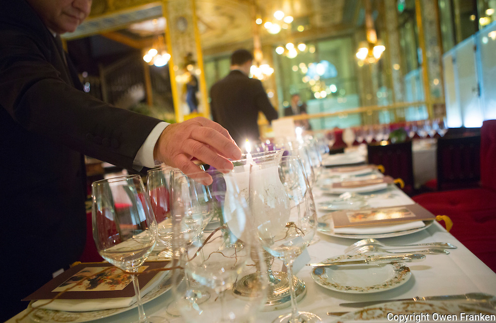 waiter lighting candles before dinner service, le Grand Vefour, Paris