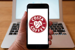 Using iPhone smartphone to display logo of Costa Coffee ,coffee shop chain