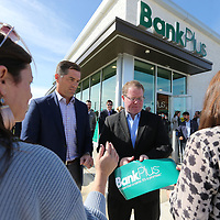Brent Waldrop, center left, and Mayor Jason Shelton unroll the ribbon to be cut to officially open the newest BankPlus branch on South Gloster Friday morning.