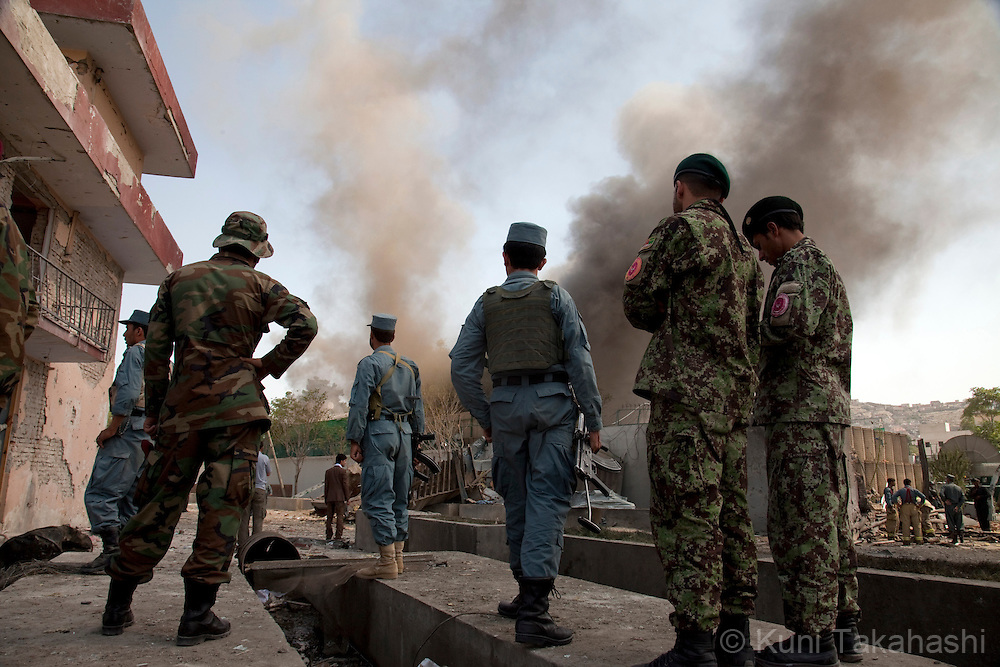 Afghan National Army soldiers and police watch heavy smoke raises from the British Council compound in Kabul, Afghanistan on Aug 19, 2011 as Afghan and British forces fight against gunmen inside. Allegedly five terrorists including suicide bombers attacked the compound, killing at least 10. .(Photo by Kuni Takahashi) .