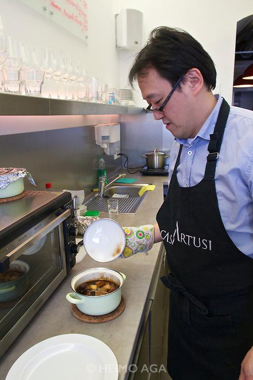 """Vienna, Austria. Kiang Winebar.<br /> Joseph Kiang preparing """"Geschmorte Schweinebauchrippchen mit Kartoffeln (Braised Pork Ribs with Potatoes)""""."""