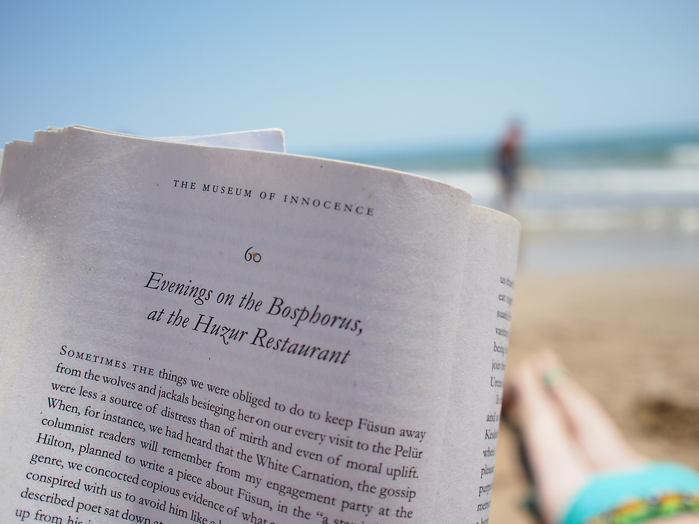 Someone reads Orhan Pamuk's Museum of Innocence on the beach in Sitges, Spain, near Barcelona, along the Mediterranean coast.