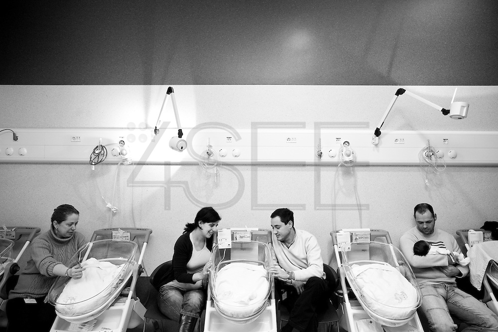 Parents with their babies. After fed newborns sleep in their cribs.<br />