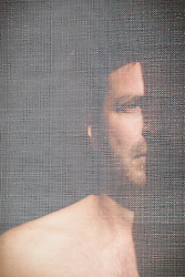 portrait of a man standing behind a screen door