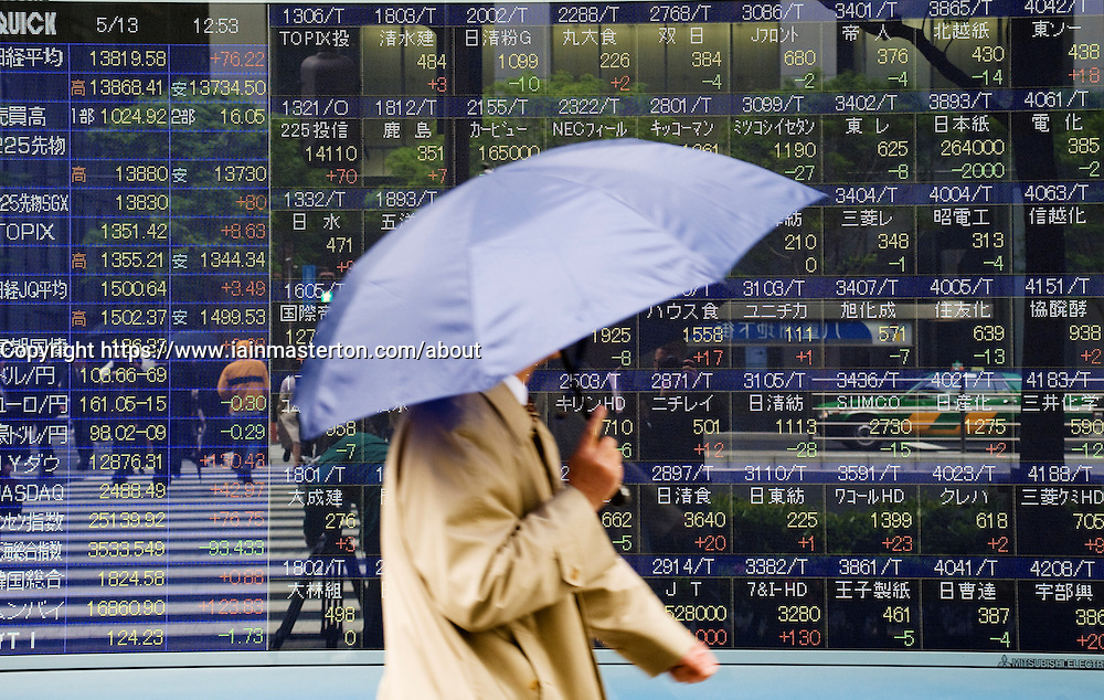Man walking past electronic stock market price information display screen on a street in Tokyo Japan