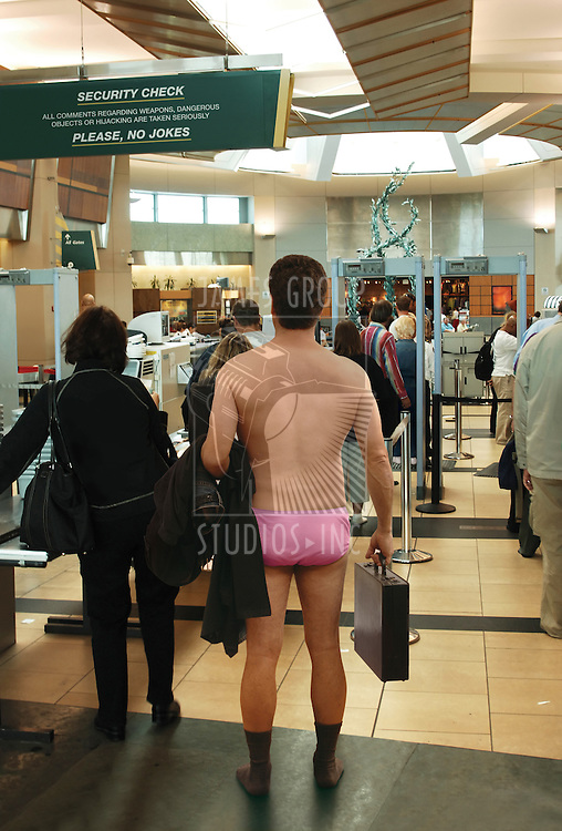 Man standing in his underwear, waiting to go through an airport security check station