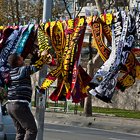 A football scarf vendor struggles with the wind, Istanbul, Turkey
