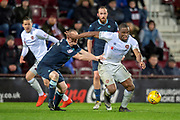 Uche Ikpeazu (#19) of Heart of Midlothian gets to the ball ahead of Steven Anderson (#5) of Partick Thistle FC during the William Hill Scottish Cup quarter final replay match between Heart of Midlothian and Partick Thistle at Tynecastle Stadium, Gorgie, Edinburgh Scotland on 12 March 2019.