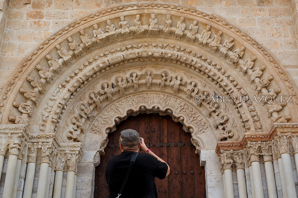 09/08/2016. A visitor photographs the North Portico of The Collegiate of Santa Maria la Mayor on August 9, 2016 in Toro, Zamora province, Spain. The Collegiate of Santa María la Mayor is a Romanesque architecture church built during the 12th and 13th centuries. Recents restorations of the Church discovered many details on its sculptures, and luthiers found the opportunity of recovering and to reproduce instruments showing on its North gate. (© Pablo Blazquez)