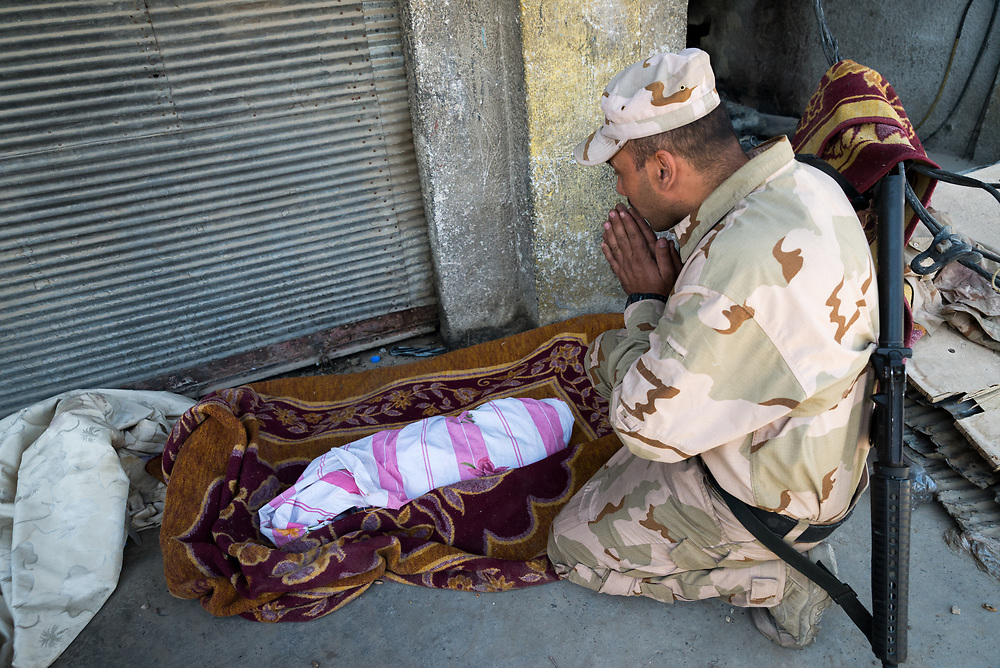 An Iraqi soldier prays next to the body of a baby outside a makeshift field clinic on the edge of Mosul's Old City as the fighting to liberate the remaining pocket of ISIS-held territory intensifies.