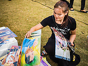 22 OCTOBER 2016 - BANGKOK, THAILAND: A mourner buys a portrait of Bhumibol Adulyadej, the King of Thailand, from a vendor on Sanam Luang. Sanam Luang, the Royal Ceremonial Ground, was packed Saturday with more than 100,000 people mourning the Monarch's death. The King died Oct. 13, 2016. He was 88. His death came after a period of failing health. Bhumibol Adulyadej was born in Cambridge, MA, on 5 December 1927. He was the ninth monarch of Thailand from the Chakri Dynasty and is also known as Rama IX. He became King on June 9, 1946 and served as King of Thailand for 70 years, 126 days. He was, at the time of his death, the world's longest-serving head of state and the longest-reigning monarch in Thai history.       PHOTO BY JACK KURTZ
