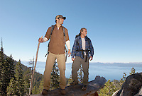Two male hikers on log near forest