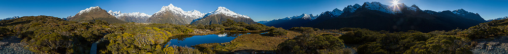 Wide panorama of Key Summit at the beginnig of the Routeburn track. The sun is coming up behind the Ailsa Mountains. Mount Christina and Mount Lyttle are directly behind the tarn.