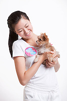 Young Asian woman carrying a puppy against white background