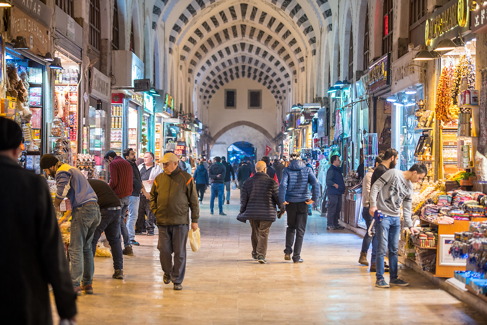 Shoppers walk up and down the main thoroughfare of the Istanbul Spice bazaar in Turkey with storefronts lining either side.