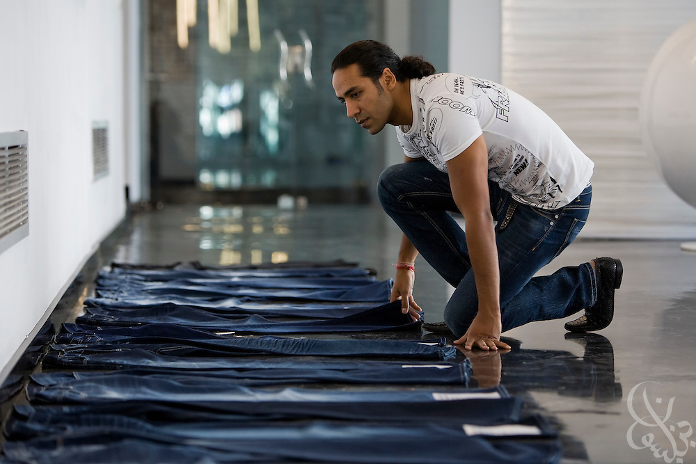 Siddharth Sinha, CEO of Vogue International Agencies FZE, inspects samples of his company's new blue jean products October 27, 2008 at the Velocity jeans factory in Ismailia (130 kilometers north of Cairo, Egypt.)  Siddharth, along with his father Air Marshal Man Mohan Sinha, have been operating their jeans factories in Egypt since 2001, employing 2700 Egyptian workers while supplying jeans to major companies that include Levis, Target, and Zara.