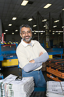 Cheerful man standing in factory with newspapers