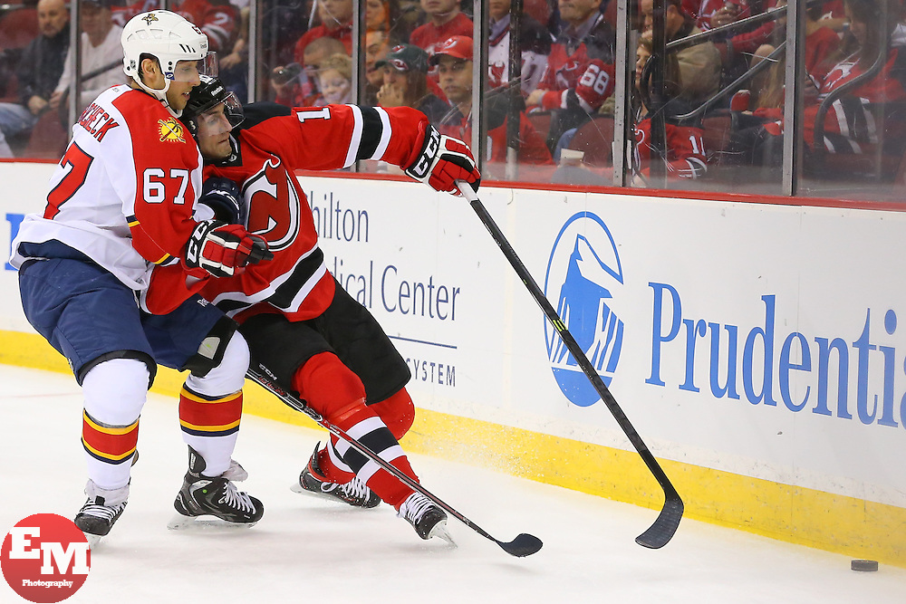 Mar 31, 2014; Newark, NJ, USA; New Jersey Devils defenseman Peter Harrold (10) and Florida Panthers center Vincent Trocheck (67) battle for the puck during the first period at Prudential Center.