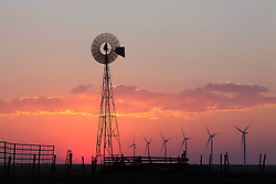 Old windmill in foreground with a row of modern windmills silhouetted at sunset in Vega, Texas.