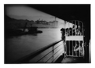 Peasants on a Yangtze River steamer gaze at the Three Gorges Dam construction site (from behind a gate barring their entry to the second-class section).  Sandouping, Hubei Province, China  1997
