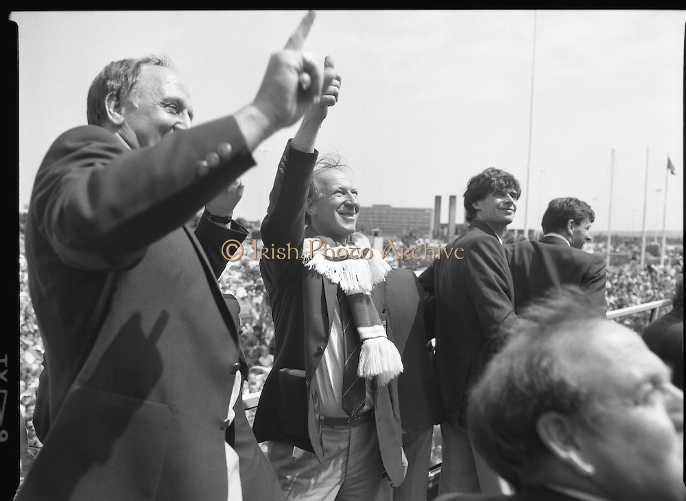 Irish Soccer Team Welcomed Home.   (R81)..1988..19.06.1988..06.19.1988..19th June 1988..After their great success in Germany in Euro 88, the Irish soccer team had a triumphant homecoming. An Taoiseach, Charles Haughey TD and his government were to the forefront of the welcome. Thousands of fans thronged the airport and all the approach roads in the hope of seeing the team. The full squad is as follows..1.GK.Packie Bonner. Celtic.2.DF.Chris Morris. Celtic.3.DF.Chris Hughton  Tottenham Hotspur.4.DF.Mick McCarthy. Celtic.5.DF.Kevin Moran. Manchester United.6.MF.Ronnie Whelan. Liverpool.7.MF.Paul McGrath. Manchester United.8.MF.Ray Houghton. Liverpool.9.FW.John Aldridge. Liverpool.10.FW.Frank Stapleton Derby County.11.MF.Tony Galvin. Sheffield Wednesday.12.FW.Tony Cascarino. Millwall.13.MF.Liam O'Brien. Manchester United.14.FW.David Kelly. Walsall.15.MF.Kevin Sheedy. Everton.16.GK.Gerry Peyton. Bournemouth.17.FW.John Byrne. Le Havre.18.FW.John Sheridan. Leeds United.19.DF.John Anderson. Newcastle United.20.FW.Niall Quinn. Arsenal..Jack Charlton and Maurice Setters salute the crowd. Niall Quinn and Packie Bonner are also in the picture.