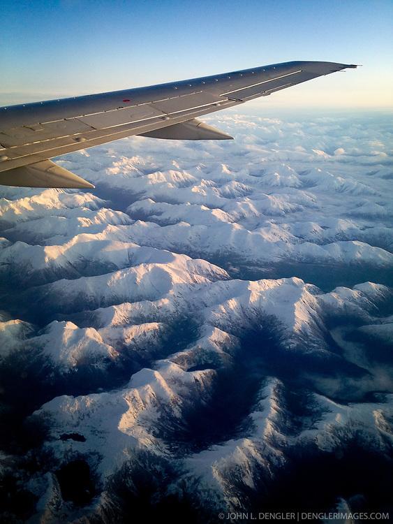 Sunrise on coastal mountains seen from Alaska Airlines flight from Seattle to Juneau in southeast Alaska.