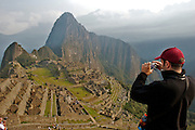 A tourist is admiring the lost Inca city of Machu Picchu, located in Cusco, Peru. Now is one of the new 7 wonder of the modern world.