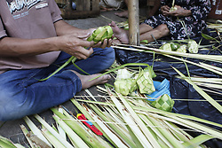 June 14, 2018 - Bogor, West Java, Indonesia - Traders  holds a bundle of ketupat, a type of rice dumpling packaged in palm leaves, in the lead up to Eid al-Fitr at a traditional market in Bogor, West Java, Indonesia. Muslims around the world are preparing to celebrate Eid al-Fitr, the three day festival marking the end of the Muslim holy month of Ramadan; it will be observed on 15th or 16th of June depending on the lunar calendar. Eid al-Fitr is one of the two major holidays in Islam. (Credit Image: © Adriana Adinandra/Pacific Press via ZUMA Wire)