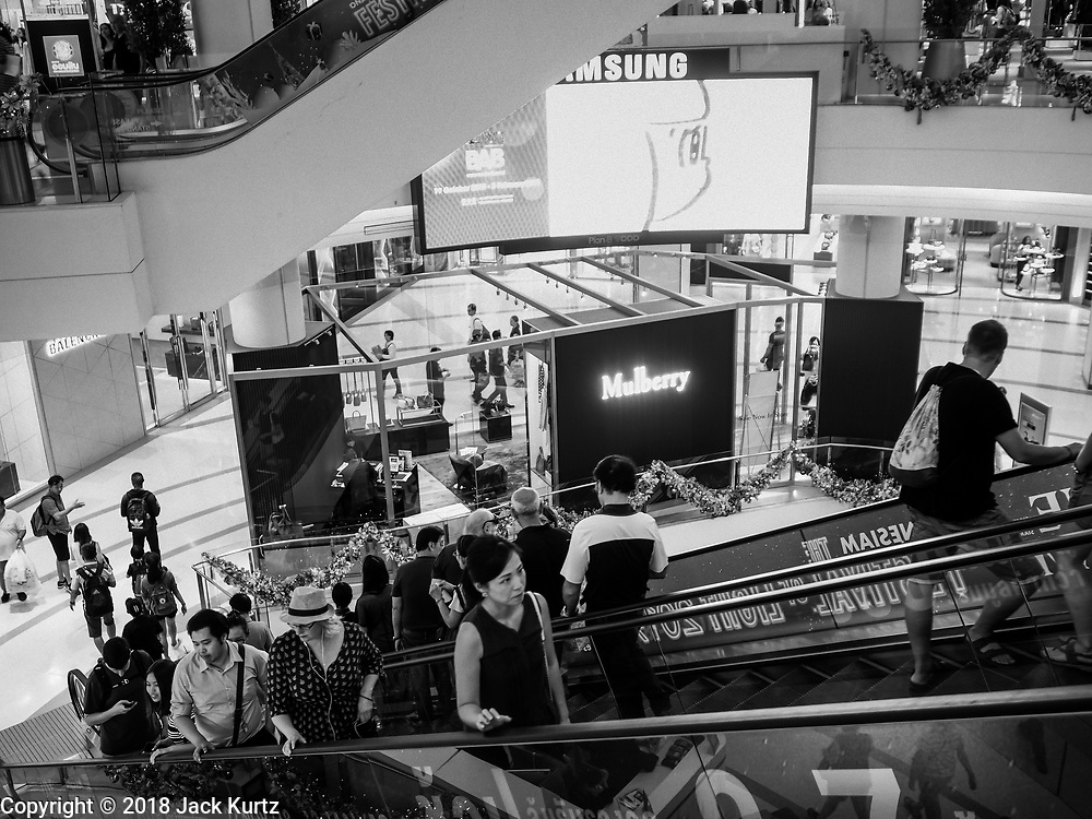 17 DECEMBER 2018 - BANGKOK, THAILAND: Shoppers on an escalator in Siam Paragon, an exclusive mall in central Bangkok. According to Credit Suisse Global Wealth Databook 2018, which surveyed 40 countries, Thailand has the highest rate of income inequality in the world. In 2016, Thailand was third, behind Russia and India. In 2016, the 1% richest Thais (about 500,000 people) owned 58.0% of the Thailand's wealth. In 2018, they controlled 66.9%. In Russia, those numbers went from 78% in 2016, down to 57.1% in 2018. The Thai government disagreed with the report and said the report didn't take government anti-poverty programs into account and that Thailand was held to an unfair standard because most of the other countries in the report are developed countries in the Organisation for Economic Co-operation and Development.   PHOTO BY JACK KURTZ