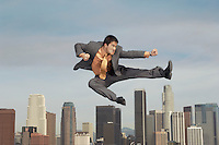 Business man doing martial arts mid-air above city