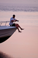 New York, Long Island - man sitting on the bow of a speeding boat.