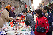 Chinese women selling souvenirs and food at market stall in Moslem district of Xian, China