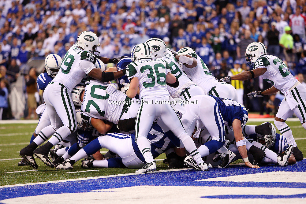 Bodies pile up and fly as the New York Jets defense makes a goal line stand on a quarterback sneak attempt by Indianapolis Colts quarterback Peyton Manning (18) during the AFC Championship football game against the Indianapolis Colts, January 24, 2010 in Indianapolis, Indiana. The Colts won the game 30-17. ©Paul Anthony Spinelli