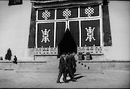 Security camera (top right of main entrance) watches over Peoples Liberation Army soldiers, likely officers, pass by the main temple halls of  Ganden Sumtseling, Tibetan Buddhist Monastery, in Gyalthang Teng (in Tibetan) in 2014 but known to the outside world as &quot;Shangri La&quot; in an attempt to attract tourism based on the 1933 novel &quot;Lost Horizon&quot;, written by James Hilton.  Kham Tibet.  (Yunnan, China)<br /> It is a temple of the Gelukpa or &ldquo;Yellow Hat&rdquo; order of Buddhism of the Dalai Lama (and Panchen Lama) which, during the time that Tibet was independent, held political power.  For the reason, the Tibetan monasteries of the Gelukpa order are more carefully watched by the central government.  The monastery, built in in 1679 under the direction of the 5th Dalai Lama, was actually bombed in the 1959 invasion of Tibet.  Later, Red Guards ramsacked the monastery during the Cultural Revolution of the 1960's and 1970's.  (They were no security cameras present during the Cultural Revolution to record the Red Guards' theft and vandalism of monastery property.)