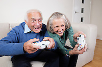 Enthusiastic senior couple playing video game at home
