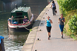 © Licensed to London News Pictures. 14/09/2016. Birmingham, West Midlands,  UK. Joggers enjoy the Indian Summer by the canal. After yesterday's thunderstorms, the weather in Birmingham, West Midlands, UK. is very warm and sunny. Photo credit: Graham M. Lawrence/LNP