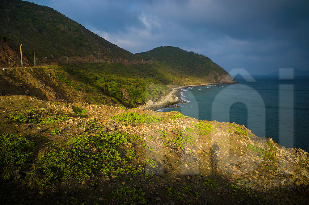 Soft sunlight illuminates coastal cliffs of Con Dao and reveals a shadowed figure, Ba Ria - Vung Tau Province, Vietnam, Southeast Asia