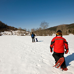 A woman and her two kids walk  through a snowy field at the Tyringham Cobble Reservation in Tyringham, Massachusetts.  Berkshire Mountains. The Trustees of Reservations.