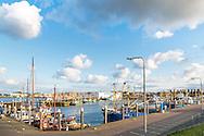 De haven van Den Oever is groter dan het dorp. Op vrijdag komen de kotters van zee. In de Vissershaven, hier op de voorgrond, mogen passanten die dat willen een plekje zoeken.