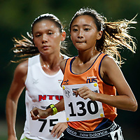 Vanessa Lee (right) of National University of Singapore overtakes Nicole Low of Nanyang Technological University with two laps remaining during the women's 5000m event. (Photo &copy; Lim Yong Teck/Red Sports) The 2018 Institute-Varsity-Polytechnic Track and Field Championships were held over three days in January.<br />