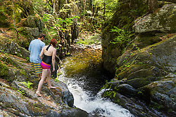 A couple explores Screw Auger Falls on Gulf Hagas Brook. Appalachian Trail. Maine's 100 Mile Wilderness.