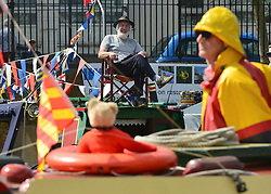 © Licensed to London News Pictures. 06/05/2013. London, UK A man sitting on a deck char watches the boat handling competition from the roof of his boat.  A Colourful gathering of canal boats in the hot bank holiday sunshine today in West London 6th May 2013. Organised by volunteers from Inland Waterways Association (IWA), The Canalway Cavalcade, which has taken place in Little Venice every year since 1983, sees around 130 boats moored along a stretch of the Grand Union Canal in London. Photo credit : Stephen Simpson/LNP