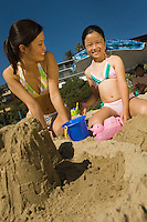 Woman Building Sandcastle With Daughter