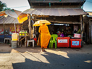 "15 FEBRUARY 2019 - SIHANOUKVILLE, CAMBODIA: A Buddhist monk collects alms at a small convenience shop a migrant camp in Sihanoukville during his morning alms rounds. Families who live in the shanty town came to Sihanoukville from other Cambodian provinces because of the town's booming economy and construction industry building Chinese resorts and casinos. There are about 80 Chinese casinos and resort hotels open in Sihanoukville and dozens more under construction. The casinos are changing the city, once a sleepy port on Southeast Asia's ""backpacker trail"" into a booming city. The change is coming with a cost though. Many Cambodian residents of Sihanoukville  have lost their homes to make way for the casinos and the jobs are going to Chinese workers, brought in to build casinos and work in the casinos.     PHOTO BY JACK KURTZ"
