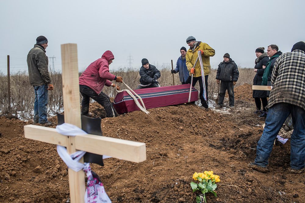 DONETSK, UKRAINE - JANUARY 30, 2015: A casket containing the body of Anatoliy Bogdan, 54, who was killed by shelling, is lowered into a grave at Yuzhnaya Cemetery on January 27 in Donetsk, Ukraine. At least seven people were killed in two shelling incidents in Donetsk today, the deadliest day for civilians in more than a week, as peace talks in the Belarussian capital of Minsk were postponed. CREDIT: Brendan Hoffman for The New York Times