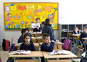 LEBANON, BEIRUT:  School classroom with children in uniforms participating in discussions about reading with full bookbags by their desks.