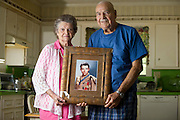 Nadene Lokey and her husband Kenneth Lokey with a photo of her brother, WWII hero Audie Murphy, at her home in Farmersville, Texas on June 17, 2013.