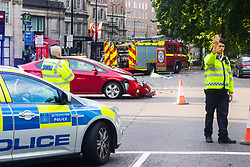 London, July 7th 2017. Emergency services attend a collision between a red Toyota Prius and an ambulance on Park Lane at the intersection of Upper Grosvenor Street. There are no reported injuries, but the ambulance was carrying a patient at the time of the collision, which has closed down all but one southbound lane on Park Lane, with surrounding streets closed to traffic. PICTURED: Police direct traffic around the scene.